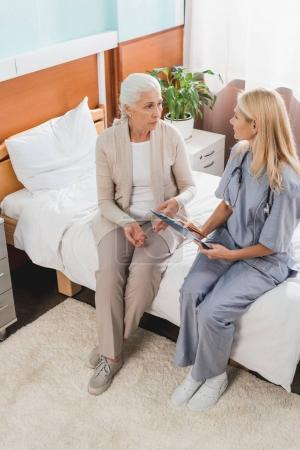Senior woman and nurse with clipboard
