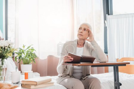 senior woman with notebook in hospital