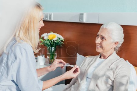 Nurse measuring temperature of patient