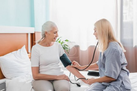 Photo for Nurse measuring blood pressure to smiling senior woman in hospital - Royalty Free Image