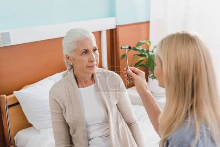 nurse examining patient with reflex hammer