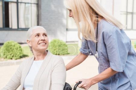 Photo pour Infirmière regardant sourire femme handicapée en fauteuil roulant - image libre de droit