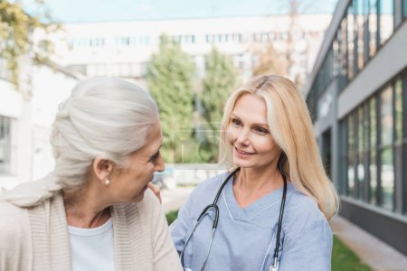 Photo for Smiling nurse looking at senior patient outside nursing home - Royalty Free Image