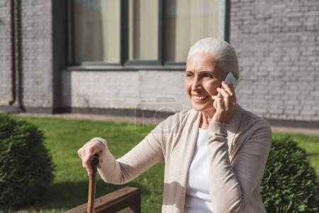 Foto de Mujer senior feliz celebración poca caña y hablando por teléfono inteligente - Imagen libre de derechos