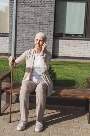 Photo pour Femme âgée souriante avec canne à pied parler sur smartphone tout en étant assis sur le banc - image libre de droit