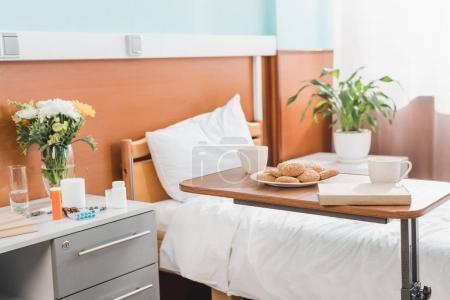 Photo pour Cookies sur la plaque, des tasses et des livres sur la table dans la salle de l'hôpital - image libre de droit