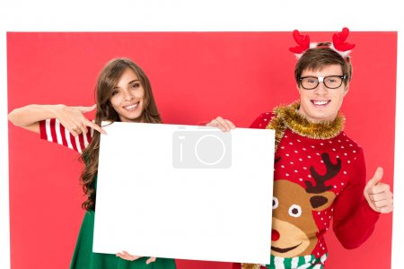 couple in christmas costumes with banner