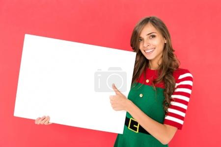 Photo for Smiling woman in elf costume with blank banner showing thumb up isolated on red - Royalty Free Image