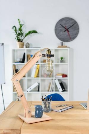 Photo pour Intérieur de bureau moderne avec table en bois, desklamp et papeterie placé dessus - image libre de droit