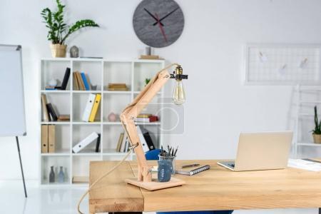 Photo pour Intérieur de bureau moderne avec table en bois, lampe de bureau et papeterie placée dessus - image libre de droit
