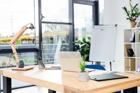 Photo pour Bureau moderne avec ordinateur portable et papeterie placé sur un bureau en bois - image libre de droit