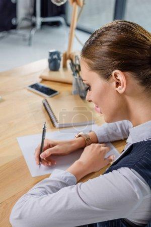 Foto de Mujer de negocios joven sentado en la oficina en su escritorio y escribir notas en papel - Imagen libre de derechos