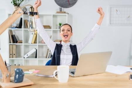 Cheering businesswoman sitting at desk