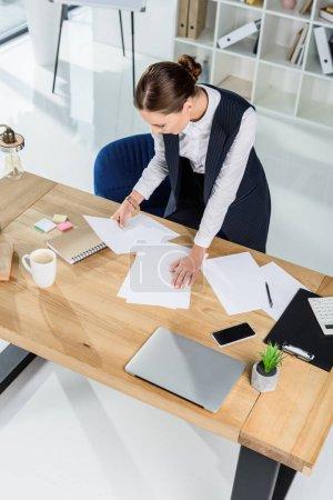 Businesswoman examining paperwork