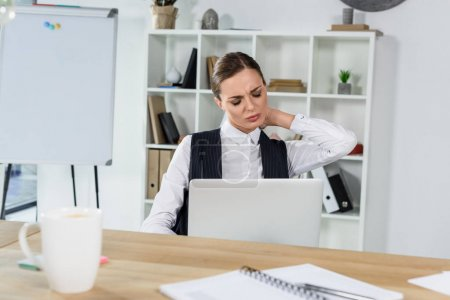 businesswoman with laptop rubbing sore neck
