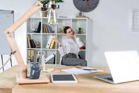 Businesswoman talking on phone in modern office