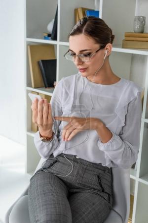 businesswoman in earphones using smartphone