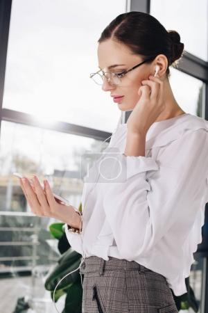 businesswoman listening to music in headphones
