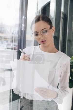 businesswoman writing on paperwork