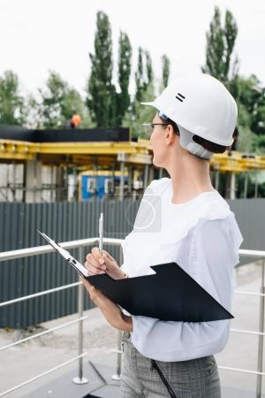 Photo for Young businesswoman in hardhat standing with folder and pen, while watching work at construction site - Royalty Free Image