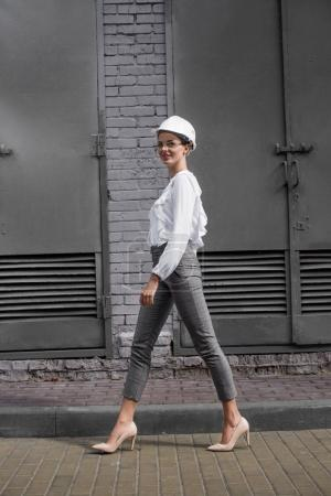 businesswoman in hardhat walking