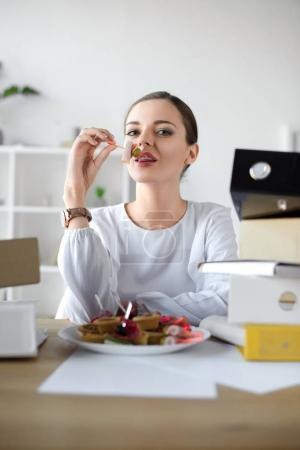 businesswoman eating tea sandwich