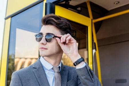 Photo pour Portrait de l'élégant jeune homme lunettes de soleil à la recherche de suite en se tenant debout près de bus de la ville - image libre de droit