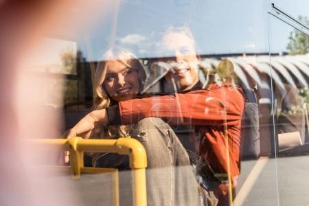Photo pour Couple souriant regardant loin tout en conduisant dans les transports publics - image libre de droit