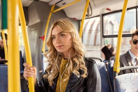 woman in earphones in city bus