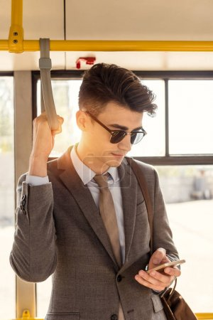 man using smartphone in city bus