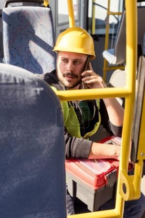 Photo pour Portrait du travailleur en casque parler sur smartphone alors qu'il circulait dans les transports publics - image libre de droit