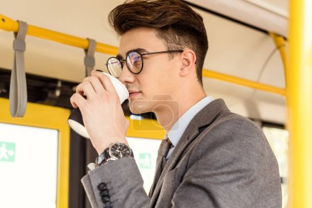 man with coffee to go in public transport