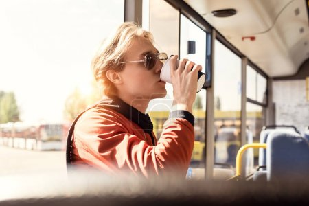 man drinking coffee in bus