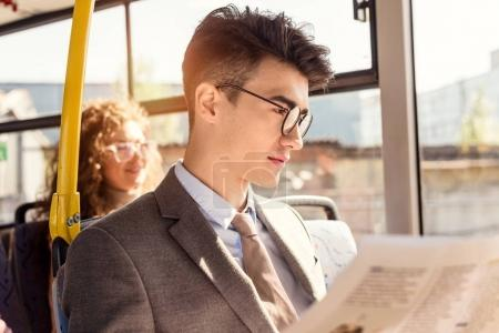 man reading newspaper in public transport