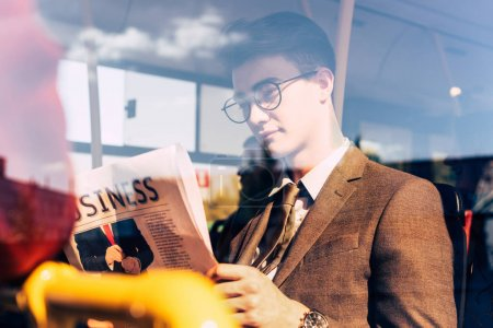man with newspaper in public transport