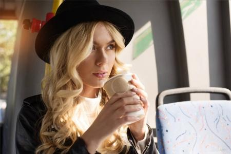 Photo for Portrait of pensive woman with coffee to go riding in public transport - Royalty Free Image