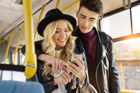 couple with smartphone in public transport