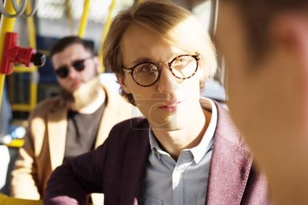 man in eyeglasses riding in city bus