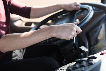 Photo for Cropped shot of bus driver holding steering wheel - Royalty Free Image