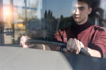 Bus driver holding steering wheel