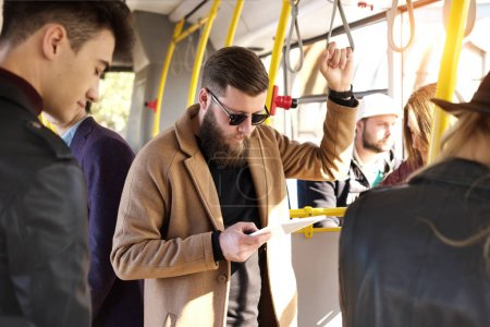 man using tablet in bus