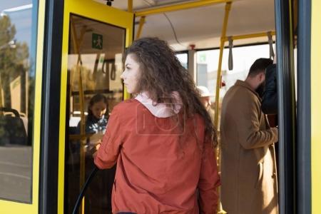 Photo pour Vue arrière du femme entrant dans les bus de la ville - image libre de droit