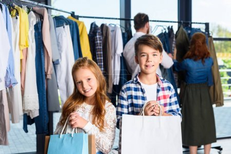 Photo for Happy children with shopping bags in boutique with parents behind - Royalty Free Image