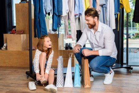 Photo pour Père et fille heureuse avec des sacs à provisions en boutique avec des vêtements et des chaussures - image libre de droit