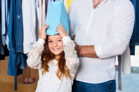 daughter with shopping bag on head