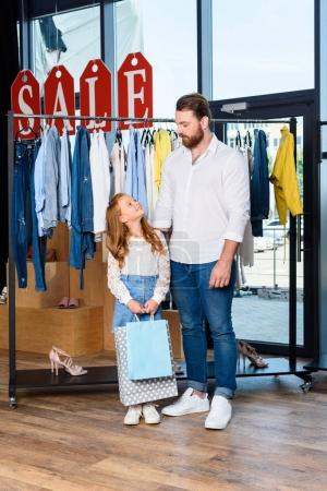 father and daughter in boutique during sale