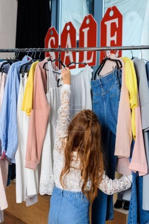 child with clothes in boutique