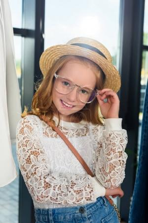 Photo for Adorable stylish child in eyeglasses and straw hat posing in boutique - Royalty Free Image