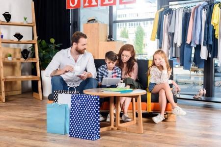 Photo pour Famille boire du café et à l'aide de tablette numérique tout en reposant sur le canapé en boutique après le shopping - image libre de droit