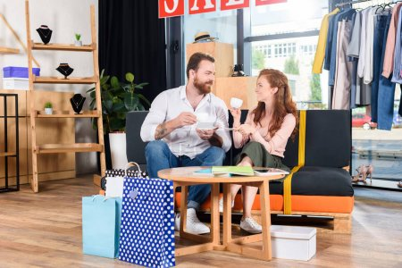 Photo for Happy couple drinking coffee and resting on sofa in boutique after shopping - Royalty Free Image